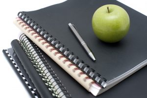 Spiral bound notebooks for taking university notes topped with a pen and fresh healthy green apple to eat as a snack while studying