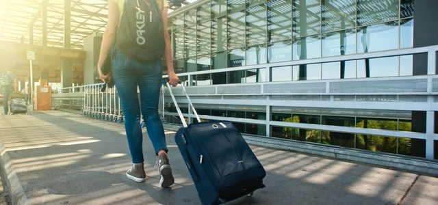 woman-walking-on-pathway-while-strolling-luggage-1008155