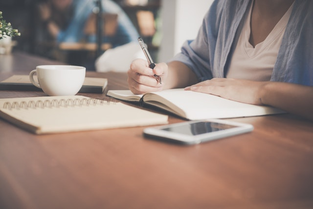 woman-writing-on-a-notebook-beside-teacup-and-tablet-733856